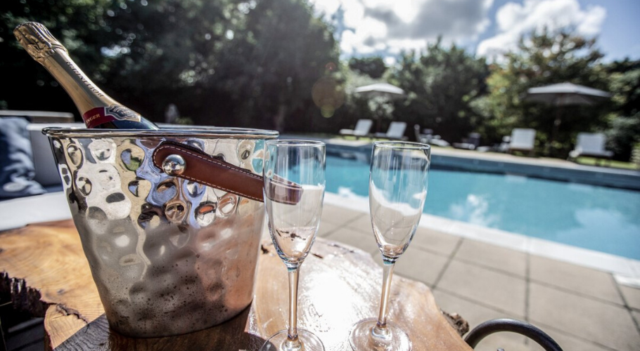Swimming pool with bottle of champagne on the table