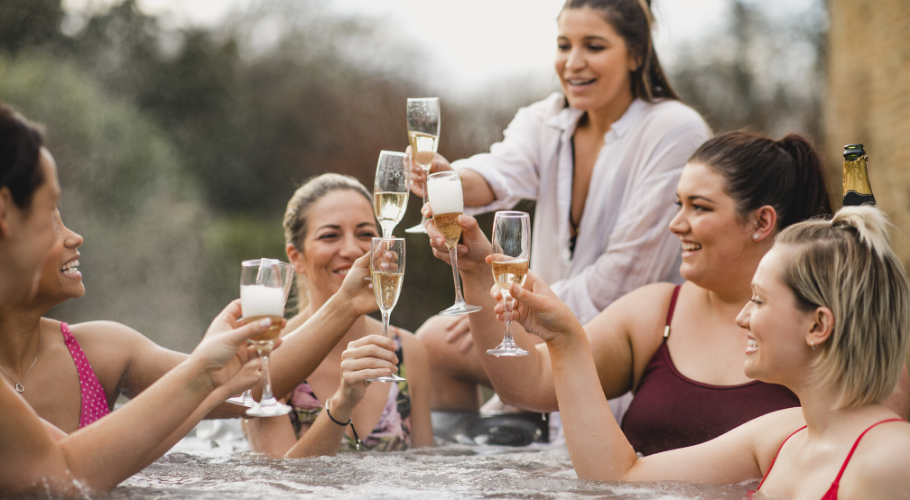 Women enjoying champagne in hot tub