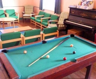 Sitting room: woodburning stove, piano and pool.