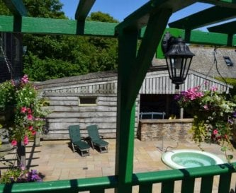 A view of the hot tub & sun terrace from BBQ area.