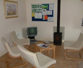 TV and lounge area with very efficient wood-burner
