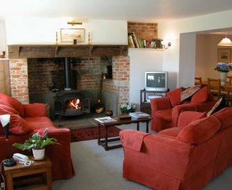 Sitting room open plan with wood burner.
